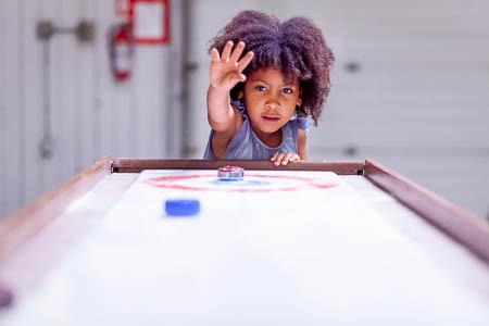 Child playing shuffle board