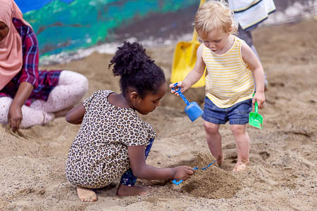 Two girls digging in the sand